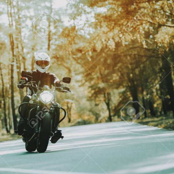 Biker In Helmet Is Riding On Highway In A Forest. Speed Vehicle. Cool rider With A Leather Jacket. Motorbike Concept. Classic Style. Ready To Drive. Speed Motorcycle In A Forest. Hidden Face.
